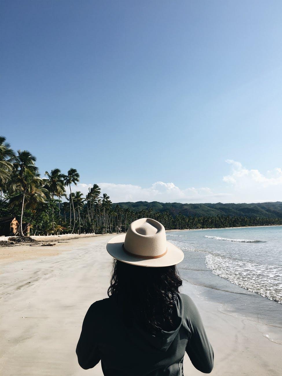 woman wearing gray jacket walking on seashore